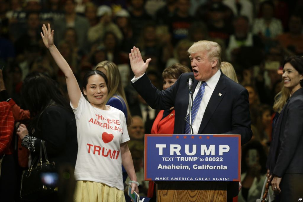 资料图片:2016年特朗普在加州安纳海姆的集会上邀请华人支持者上台接受鼓掌。(美联社)