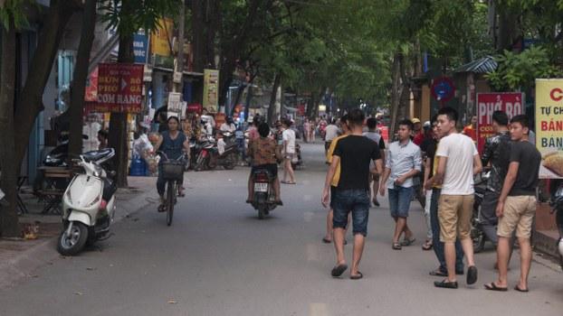 图说:越南河内市近郊的纸桥郡,是最著名的劳务街,短短600公尺的街道聚集上百家中介公司,输出劳工到日本、韩国、台湾等地打工。晚餐时间,街上都是准备出国打工的年轻工人。(摄影/简永达)