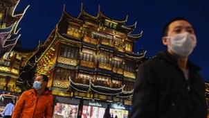 美国确诊人数超过中国,但中国的疫情真的稳住了吗?图为民众戴着口罩经过上海豫园。(法新社)