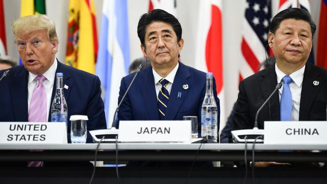 在日本大坂举行的二十国集团会议,重头戏是美国总统特朗普(左)和中国国家主席习近平(右)两人在美中贸易谈判之间的较量。中间为日本首相安倍晋三。(法新社)