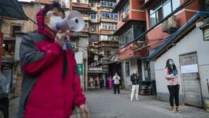 2020年3月18日,武汉居民在排队等待领取购买的猪肉。(法新社)