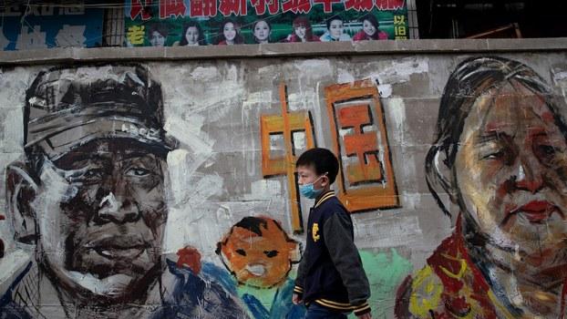 2020年4月24日,一名儿童戴着口罩走过武汉街头。(法新社)