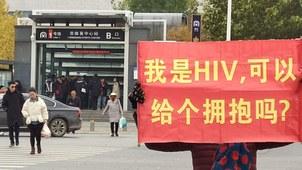 """三名女性艾滋病毒感染者在郑州街头希望以""""抱抱团""""行为艺术,也就是和路人拥抱的方式,对艾滋病传播途径进行科普。其中叫小露(网名)的女性手举一张牌子,上写""""我是HIV,可以给个拥抱吗?""""(受访者提供)"""