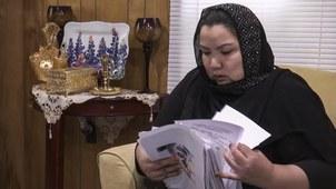 来自新疆的维吾尔人Zumret Dawut在美国弗吉尼亚的家里展示新疆实行强制计划生育的资料。(美联社)