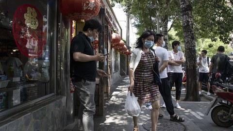 中国经济复苏后又面临困难。图为2020年7月1日一个女子提着食物离开北京的一个餐厅。(美联社)
