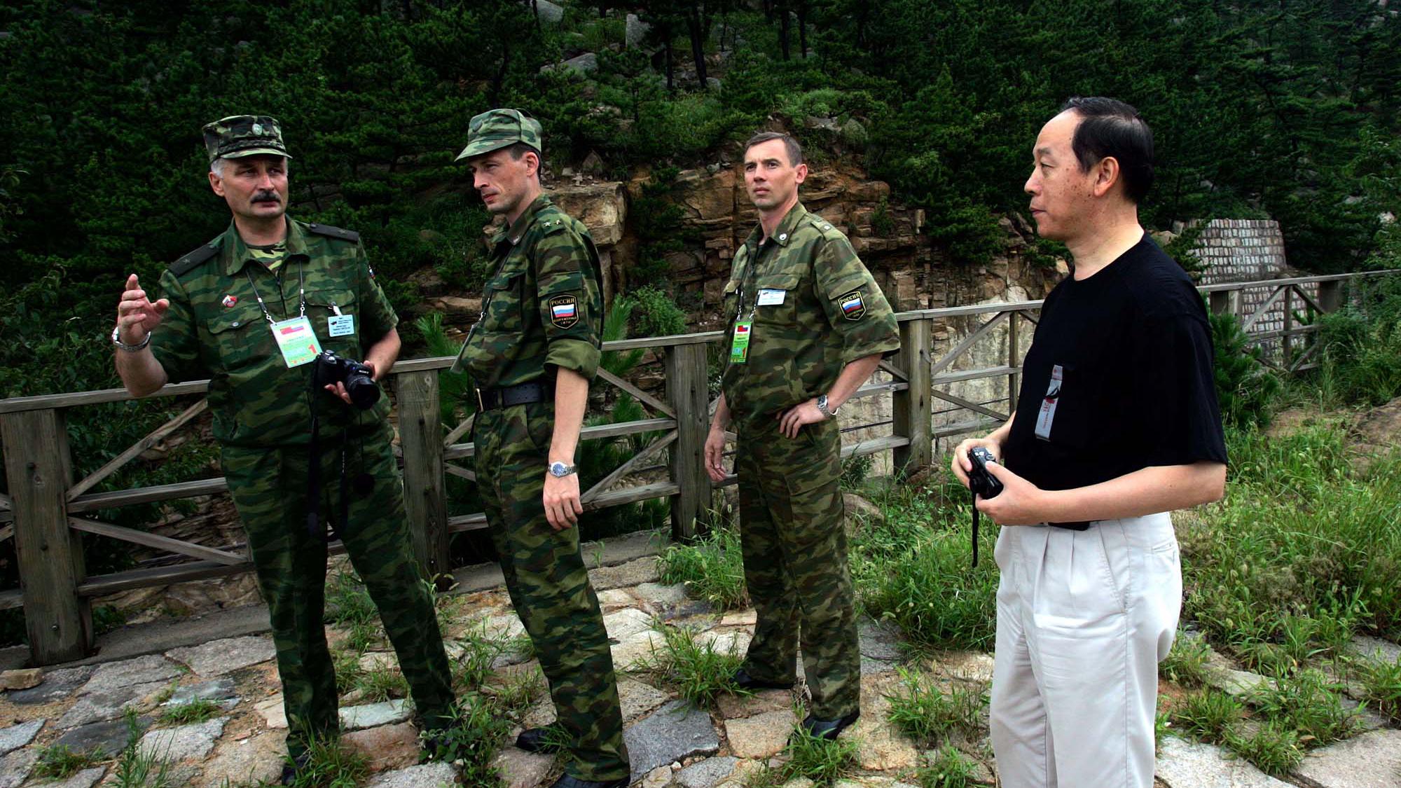 2005年8月,俄中两国首次展开联合军演。图为军演中的俄国士兵在和一名中国男子谈话。(美联社)