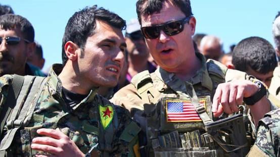 今后美国反恐任务将更多交给当地民兵组织。图为一名美军军官与库德族人民保卫军战士交谈。(Getty Images)