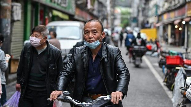 2020年4月8日,武汉市一名民众戴着口罩在骑自行车。(法新社)