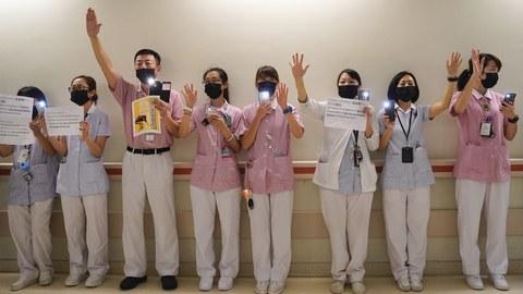 香港医护工作者在抗议,举起五个指头表示五大诉求一不可缺。(美联社)