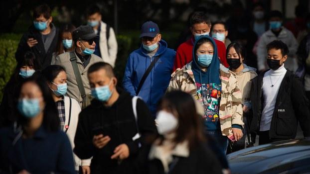 资料图片:2020年10月29日,戴着口罩的人们穿过北京商务中心区。(美联社)