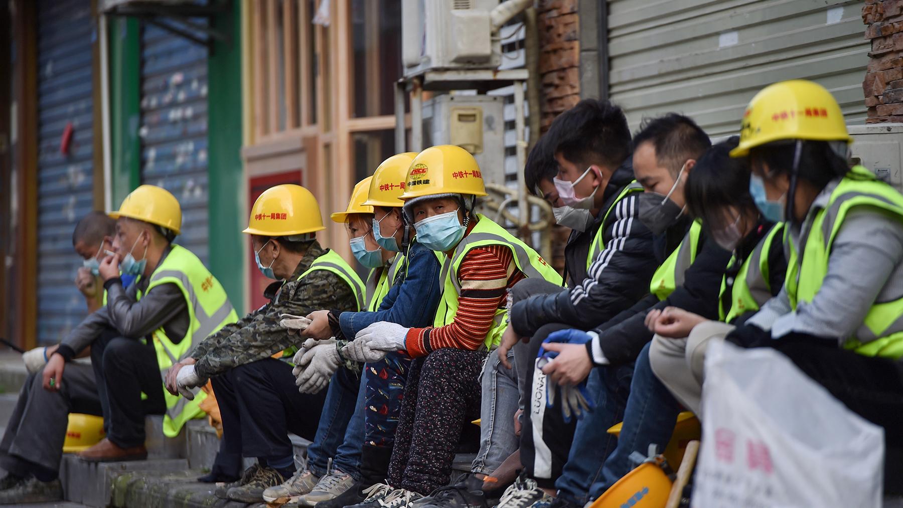 2020年2月23日,在武汉一所医院里设置路障的工人在短暂休息。(法新社)