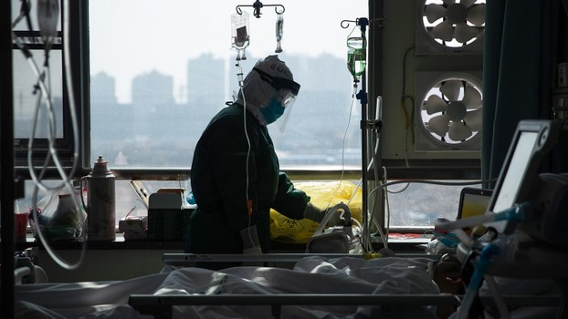 2020年2月23日,一名医生在武汉一所医院里治疗武汉肺炎患者。(法新社)