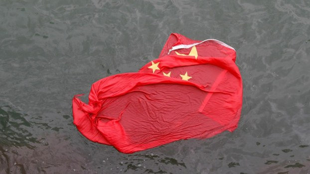 香港示威抗议者将升起的大陆国旗拆走抛下海。(美联社)