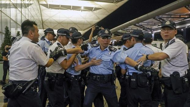 香港警察在香港机场执勤时暂时后退。(美联社)