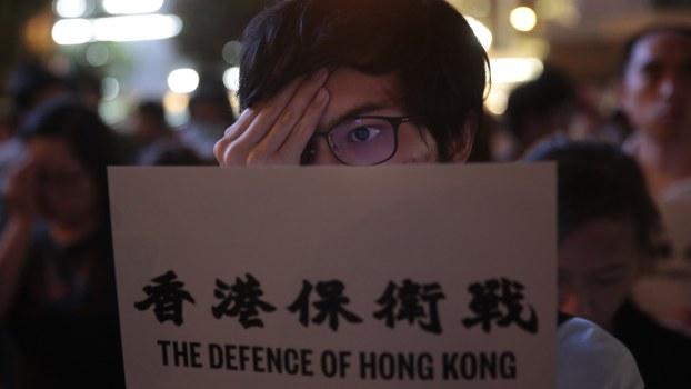 """一名香港抗议者举着""""香港保卫战""""的牌子。(美联社)"""