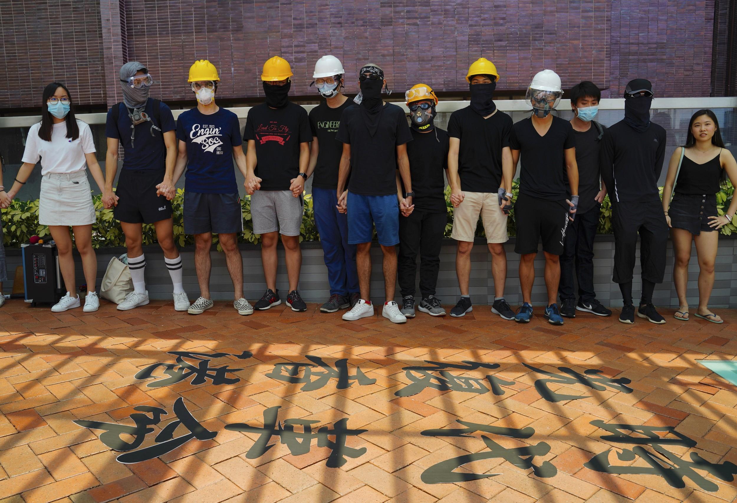 """2019年9月9日,香港抗议者在地上写下""""光复香港,时代革命""""的抗议标语。(美联社)"""