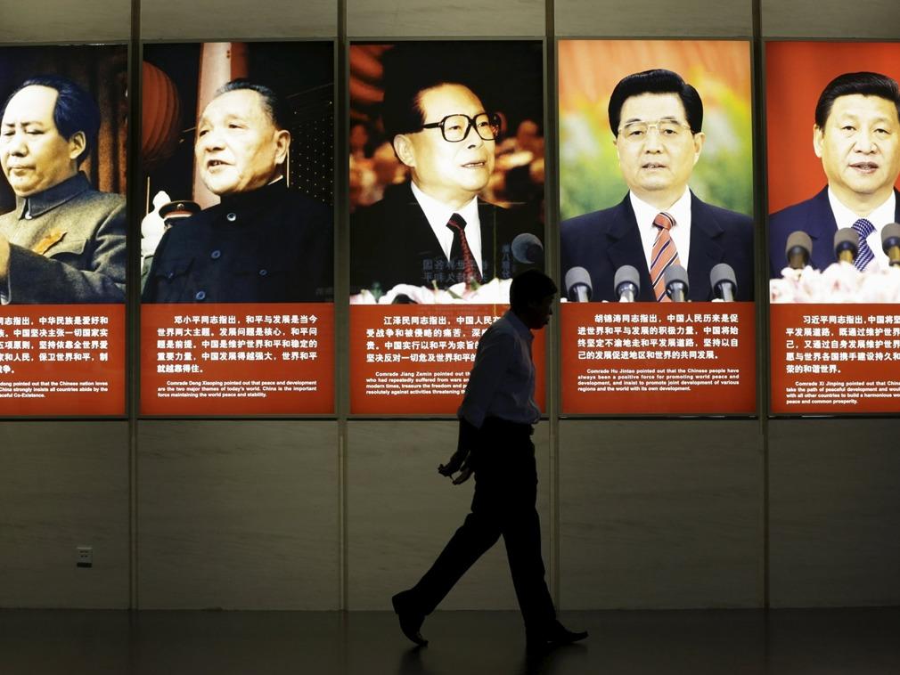 2015年7月7日,一名民众从中国五代领导人毛泽东、邓小平、江泽民、胡锦涛、习近平的画像前走过。(Reuters)