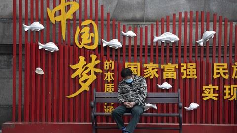 """2020年4月1日,一名男子坐在中国武汉的一个""""中国梦""""宣传广告前打盹。(法新社)"""