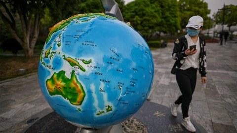 2020年4月8日,武汉一名民众走过公园里的一个地球模型。(法新社)