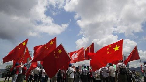 2020年6月30日,支持中国政府的香港民众高举中国国旗。(美联社)