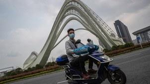 2020年3月26日航拍下的武汉街头情景,有民众戴口罩骑摩托车出行。(法新社)