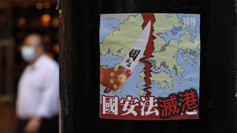 """2020年7月2日,一名香港民众走过抗议者留下的""""国安法灭港""""标语前。(美联社)"""