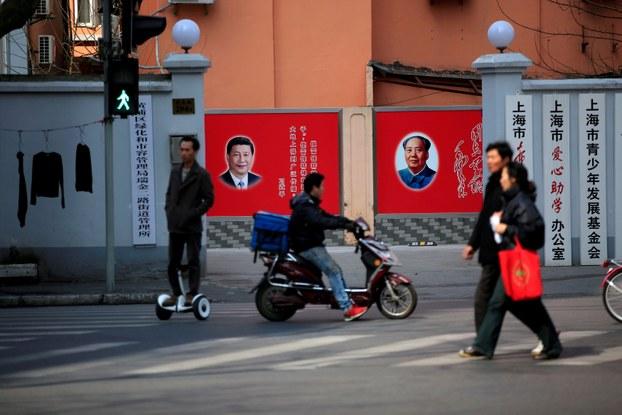 图为上海一家单位门内挂有习近平与毛泽东像的墙壁宣传画。(Reuters)